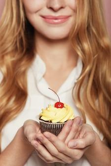Vrouwenhanden die een heerlijke yummy cupcake houden