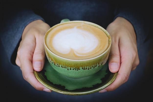 Vrouwenhanden die een kop van koffie met de vorm van de hartvorm latte houden
