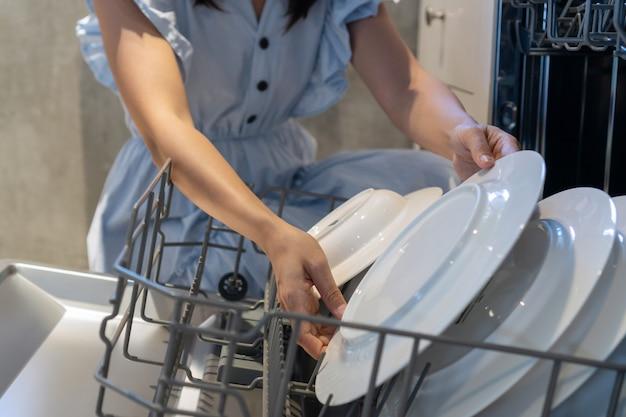 Vrouwenhanden die een plaat thuis zetten in de afwasmachine. detailopname