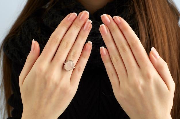 Vrouwenhanden die een ring en een mooie manicure tonen