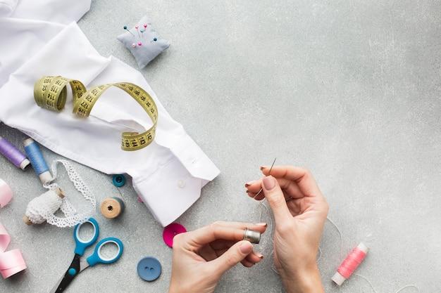 Vrouwenhanden die een wit overhemd met exemplaarruimte naaien