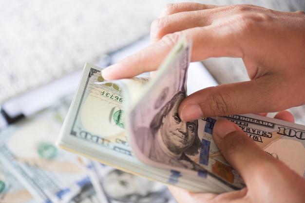 Vrouwenhanden die en bos van de dollarsbankbiljetten van amerika houden tellen