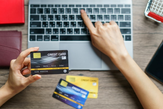 Vrouwenhanden die en craditkaart voor online het winkelen houden gebruiken.