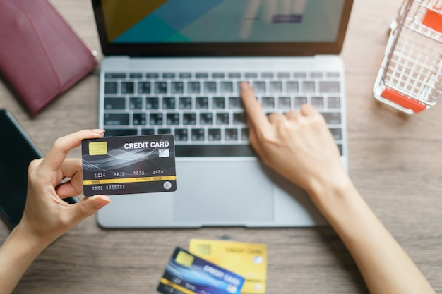Vrouwenhanden die en creditcard voor online het winkelen houden gebruiken.