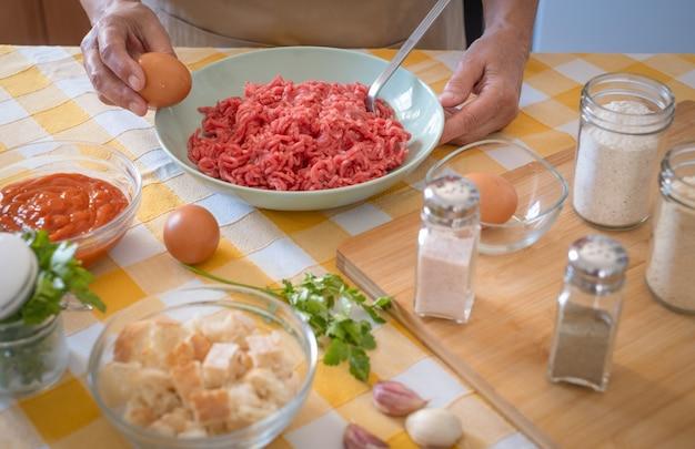 Vrouwenhanden die gehaktballen bereiden met te mengen grondstoffen, huiskeuken en geel tafelkleed