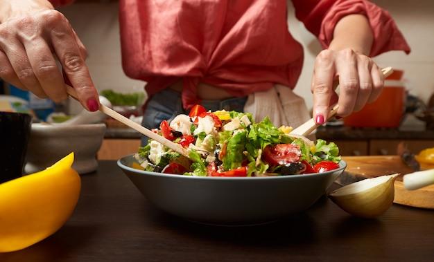 Vrouwenhanden die gezonde griekse salade mengen