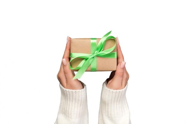 Vrouwenhanden die gift houden verpakken en verfraaid