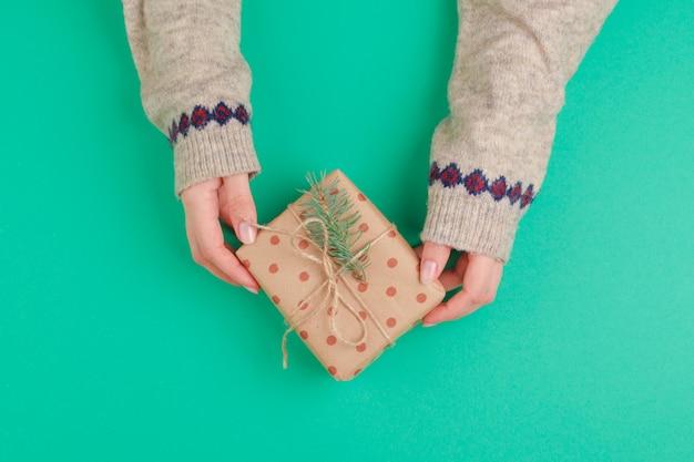 Vrouwenhanden die giftdoos op groen houden