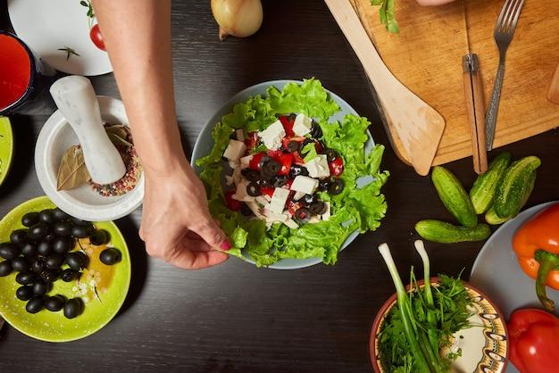 Vrouwenhanden die griekse salade voorbereiden