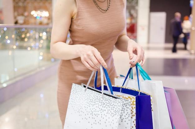 Vrouwenhanden die het winkelen zakken in het winkelcomplex houden