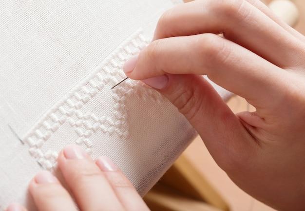 Vrouwenhanden die kruissteek doen. een close-up van borduurwerk.