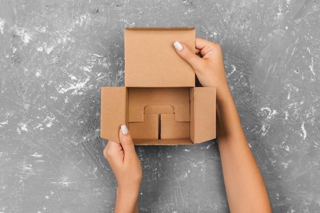 Vrouwenhanden die lege doos houden