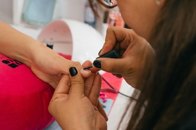 Vrouwenhanden die manicure in salon doen.