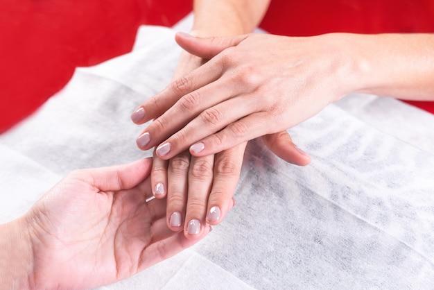 Vrouwenhanden die manicure na professionele spijkerbehandeling in salon tonen