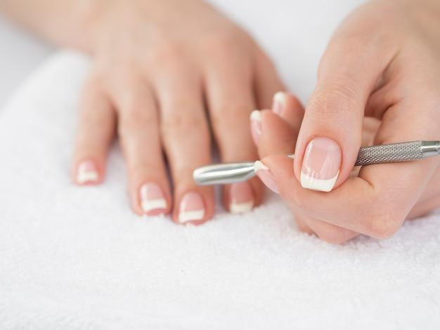 Vrouwenhanden die manicurehulpmiddel houden