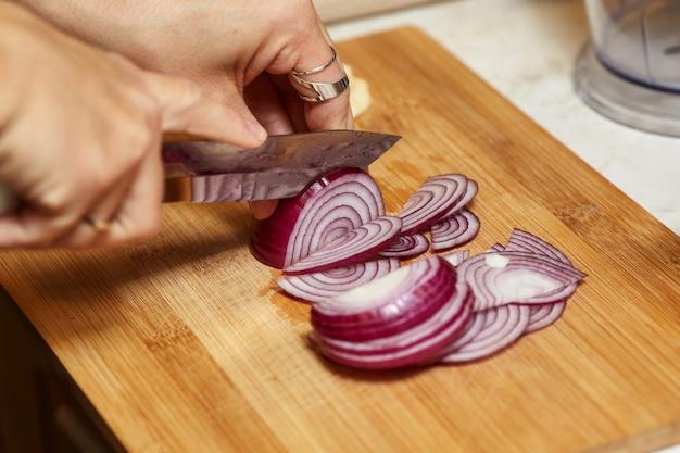 Vrouwenhanden die mes houden en rode ui in keuken hakken