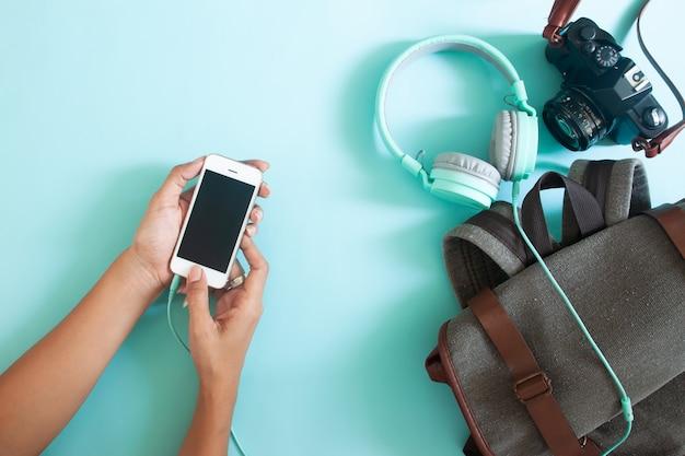 Vrouwenhanden die mobiele telefoon met reisrugzak en camera met behulp van. bovenaanzicht op kleur achtergrond