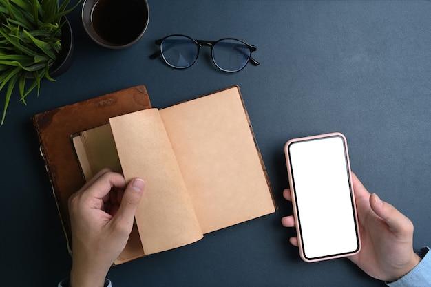 Vrouwenhanden die mock-up smartphone vasthouden en notitieboekje openen op zwart leer.