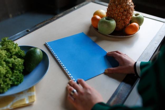 Vrouwenhanden die notitieboekje, op keukenlijst met vruchten en saladeavocado houden.
