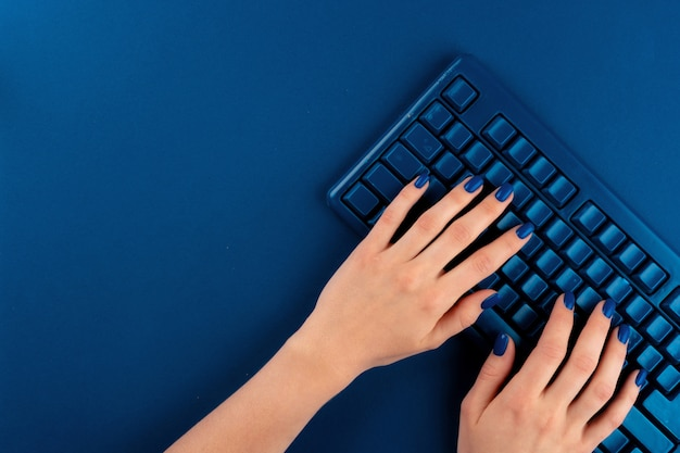 Vrouwenhanden die op computertoetsenbord typen met klassieke blauwe kleur