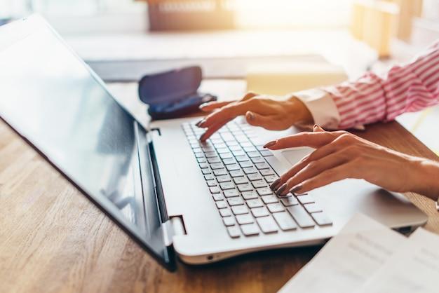 Vrouwenhanden die op het toetsenbord typen werk thuis.