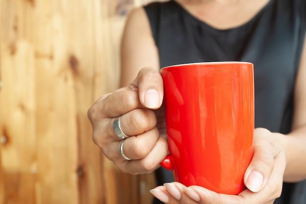 Vrouwenhanden die rode kop van koffie houden. detailopname
