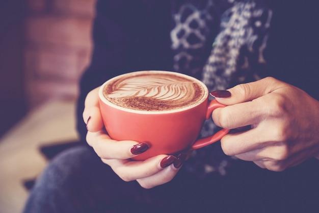Vrouwenhanden die rode kop van koffie latte houden