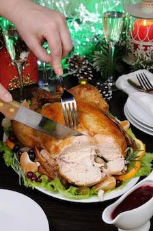 Vrouwenhanden die smakelijke, sappige, pittige smakelijke geroosterde hele kip in plakjes snijden