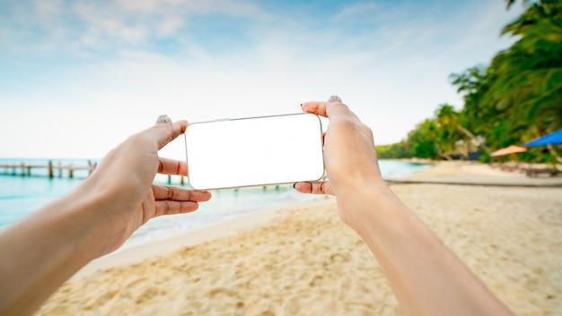Vrouwenhanden die smartphone met lege het schermvertoning houden op zandstrand van tropisch eiland. vrouw die een foto van paradijsstrand neemt op de zomervakantie.