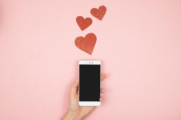 Vrouwenhanden die smartphone op roze oppervlakte met exemplaarruimte houden. plat leggen. bovenaanzicht mockup-sjabloon voor valentijnsdag.