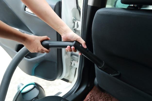 Vrouwenhanden die stofzuiger binnenlandse auto met behulp van