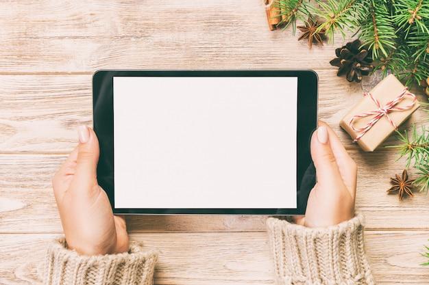 Vrouwenhanden die tabletcomputer op houten lijstlijst met cristmas het winkelen tijd met behulp van,