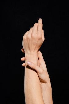 Vrouwenhanden die verschillende gebaren over donkere achtergrond tonen (foto met uitknippad)