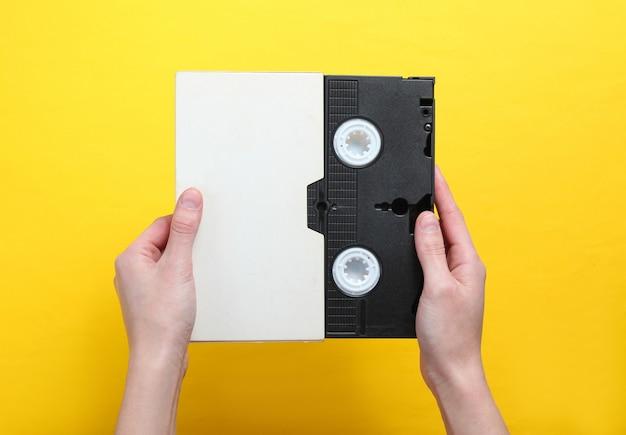 Vrouwenhanden die videocassette in dekking, videoband op een gele achtergrond houden hoogste mening, minimalisme.