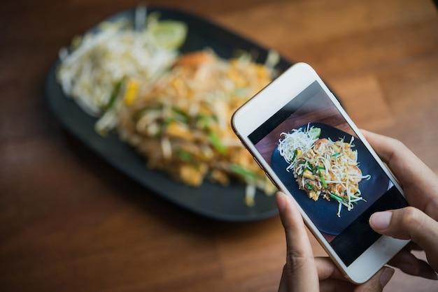 Vrouwenhanden die voedselfoto nemen door mobiele telefoon
