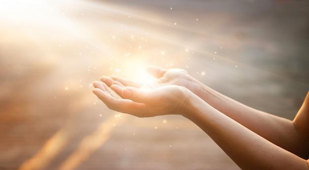Vrouwenhanden die voor zegen van god op zonsondergangachtergrond bidden