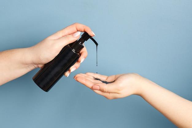 Vrouwenhanden die zwarte reinigingsolie met houtskool aanbrengen om de huid te reinigen
