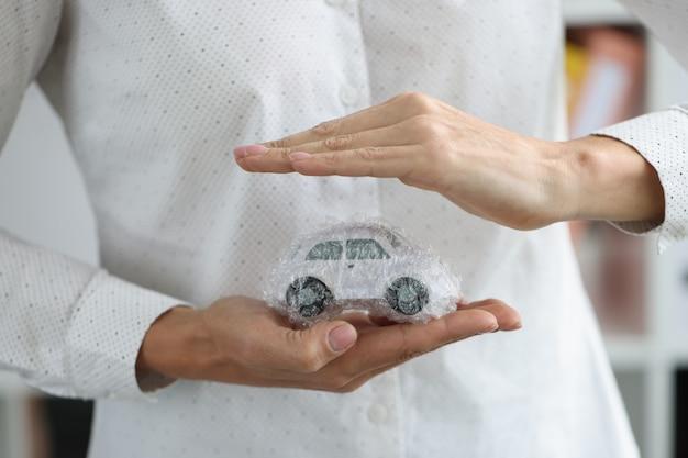 Vrouwenhanden en auto in verpakkingszak als concept van de beschermingsvoertuigverzekering