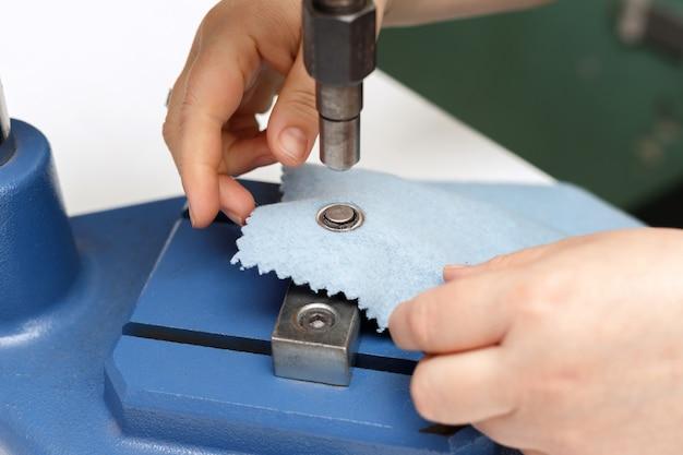 Vrouwenhanden en een klinknagelmachine op de stof