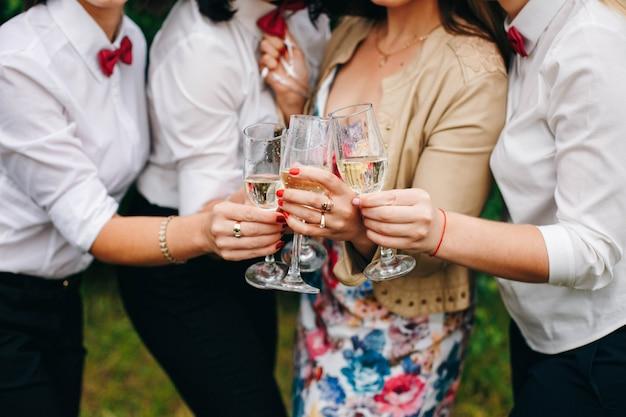Vrouwenhanden en glazen champagne. vier een vrijgezellenfeest.