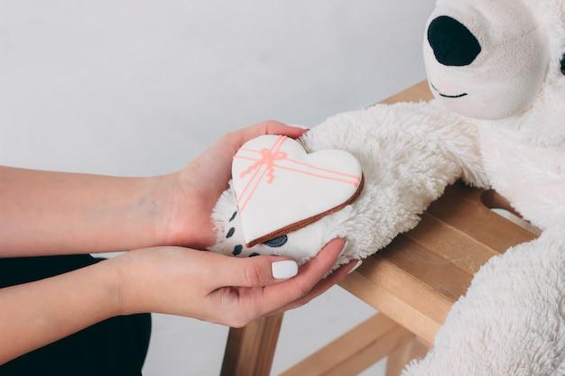 Vrouwenhanden en witte hartpeperkoek op poot van oud beerstuk speelgoed