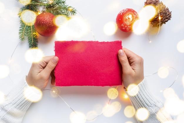 Vrouwenhanden, gekleed in een witte trui, houden een vel handgeschept rood papier vast. kerst lege wenskaart