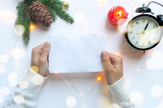 Vrouwenhanden, gekleed in een witte trui, houden een vel handgeschept wit papier vast. kerst lege wenskaart