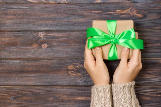 Vrouwenhanden geven huidige geschenkdoos bovenaanzicht