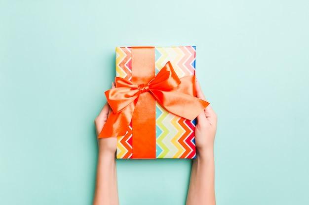 Vrouwenhanden geven verpakt kerst- of ander met de hand gemaakt kerstcadeau in gekleurd papier