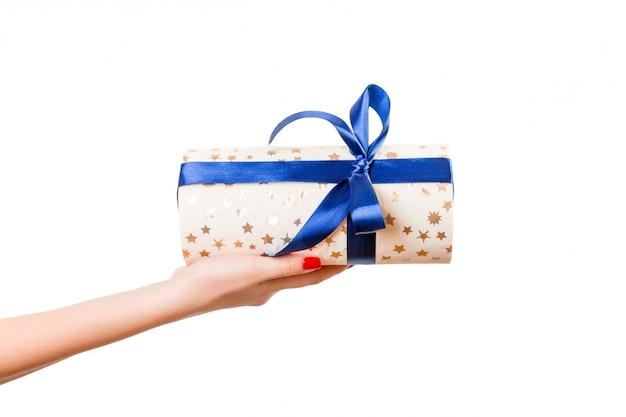 Vrouwenhanden geven verpakt kerst- of ander vakantie-handgemaakt cadeau in goud papier met blauw lint.