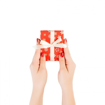 Vrouwenhanden geven verpakt kerst- of ander vakantie-handgemaakt cadeau in rood papier met gouden lint.