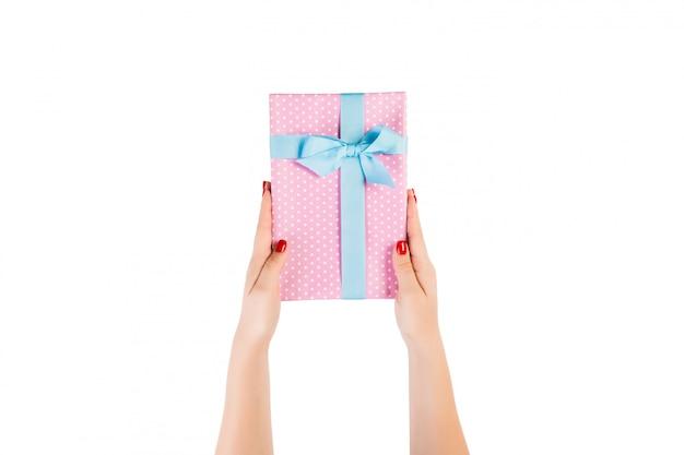 Vrouwenhanden geven verpakt kerst- of ander vakantie-handgemaakt cadeau in roze papier met blauw lint