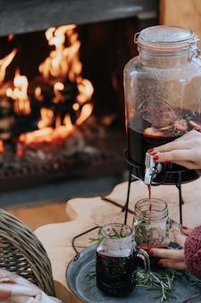 Vrouwenhanden gieten glühwein buitenshuis en een brandende open haard