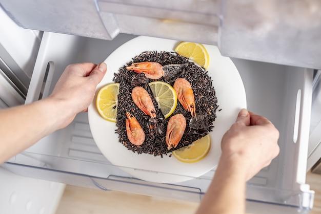 Vrouwenhanden halen een bord zwarte rijst, garnalen en citroen uit de vriezer van de koelkast